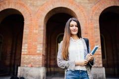 Adolescente sonriente con las carpetas y bolso en la formación universitaria Fotos de archivo libres de regalías