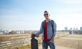 Adolescente sonriente con longboard en la calle Fotos de archivo