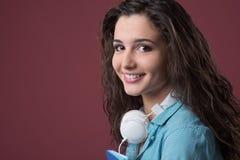 Adolescente sonriente con los auriculares Fotografía de archivo