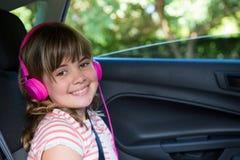 Adolescente sonriente con los auriculares en el asiento trasero del coche Imágenes de archivo libres de regalías