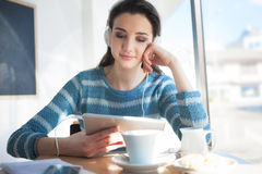 Adolescente sonriente con los auriculares en la barra Imagen de archivo libre de regalías