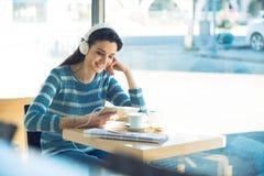 Adolescente sonriente con los auriculares en la barra Imagen de archivo