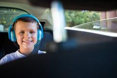 Adolescente sonriente con los auriculares que se sientan en el asiento trasero del coche Foto de archivo libre de regalías