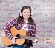 Adolescente sonriente con los auriculares, tocando la guitarra Fotos de archivo