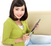 Adolescente sonriente con PC de la tableta Imágenes de archivo libres de regalías