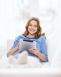 Adolescente sonriente con PC de la tableta en casa Foto de archivo libre de regalías