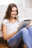 Adolescente sonriente con PC de la tableta en casa Imagen de archivo