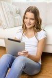 Adolescente sonriente con PC de la tableta en casa Imágenes de archivo libres de regalías