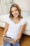 Adolescente sonriente con PC de la tableta en casa Fotografía de archivo
