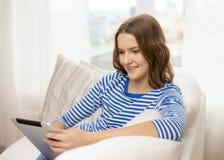Adolescente sonriente con PC de la tableta en casa Imagenes de archivo