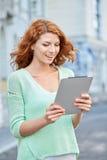 Adolescente sonriente con PC de la tableta en la calle de la ciudad Imagenes de archivo