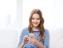 Adolescente sonriente con smartphone en casa Foto de archivo libre de regalías