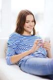 Adolescente sonriente con smartphone en casa Imagen de archivo libre de regalías