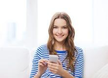 Adolescente sonriente con smartphone en casa Imágenes de archivo libres de regalías