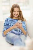 Adolescente sonriente con smartphone en casa Fotografía de archivo libre de regalías