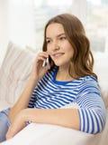 Adolescente sonriente con smartphone en casa Imagen de archivo
