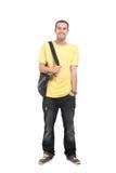 Adolescente sonriente con una cartera que se coloca en el fondo blanco Fotografía de archivo