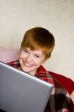 Adolescente sonriente con una computadora portátil Imagen de archivo