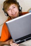Adolescente sonriente con una computadora portátil Imagen de archivo libre de regalías