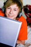 Adolescente sonriente con una computadora portátil Imágenes de archivo libres de regalías