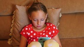 Adolescente sonriente de la muchacha que usa el teléfono móvil en sala de estar interior del sofá acogedor metrajes