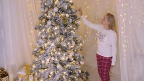Adolescente sonriente de la muchacha que viene al árbol del Año Nuevo del día de fiesta en sala de estar del milagro almacen de video