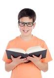 Adolescente sonriente de trece que lee un libro Imágenes de archivo libres de regalías