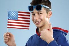 Adolescente sonriente del estudiante masculino de los jóvenes que sostiene una bandera Foto de archivo libre de regalías