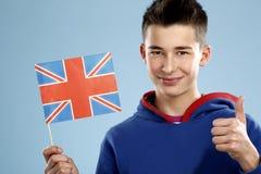 Adolescente sonriente del estudiante masculino de los jóvenes que sostiene una bandera Imagenes de archivo