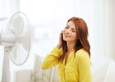 Adolescente sonriente del pelirrojo con la fan grande en casa Foto de archivo libre de regalías