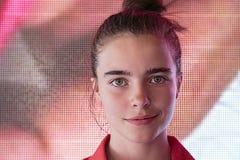 Adolescente sonriente delante de una pantalla digital Fotos de archivo libres de regalías