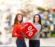 Adolescente sonriente dos con la muestra del por ciento en la caja Fotos de archivo libres de regalías