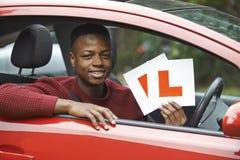 Adolescente sonriente en el coche que pasa conduciendo el examen Fotografía de archivo