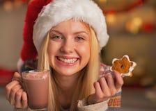 Adolescente sonriente en el sombrero de santa con la taza de chocolate caliente Fotos de archivo libres de regalías
