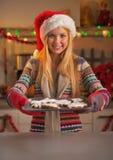 Adolescente sonriente en el sombrero de santa que muestra la cacerola de galletas frescas Foto de archivo