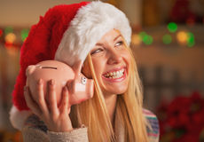 Adolescente sonriente en el sombrero de santa que sacude la hucha Fotografía de archivo libre de regalías