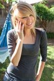 Adolescente sonriente en el teléfono móvil Imagenes de archivo