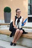 Adolescente sonriente en el uniforme escolar que se sienta en banco Imágenes de archivo libres de regalías