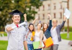 Adolescente sonriente en esquina-casquillo con el diploma Fotos de archivo libres de regalías