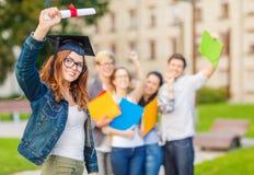 Adolescente sonriente en esquina-casquillo con el diploma Imagen de archivo libre de regalías