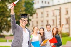 Adolescente sonriente en esquina-casquillo con el diploma Foto de archivo libre de regalías