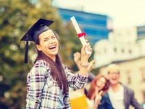 Adolescente sonriente en esquina-casquillo con el diploma Imágenes de archivo libres de regalías