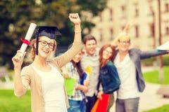 Adolescente sonriente en esquina-casquillo con el diploma Imagen de archivo