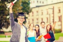 Adolescente sonriente en esquina-casquillo con el diploma Fotografía de archivo