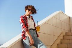 Adolescente sonriente en gafas de sol que bebe el zumo de naranja Imagen de archivo