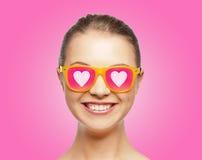 Adolescente sonriente en gafas de sol rosadas Fotografía de archivo