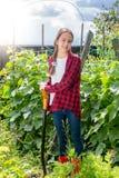 Adolescente sonriente en la camisa a cuadros roja que presenta con la pala en el jardín Imagenes de archivo