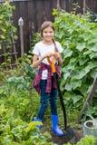 Adolescente sonriente en las botas de goma azules que trabajan en jardín con la espada Imagenes de archivo