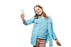 Adolescente sonriente en las lentes que toman el selfie con smartphone aislado en blanco Fotografía de archivo