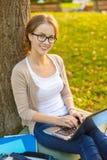 Adolescente sonriente en lentes con el ordenador portátil imagen de archivo